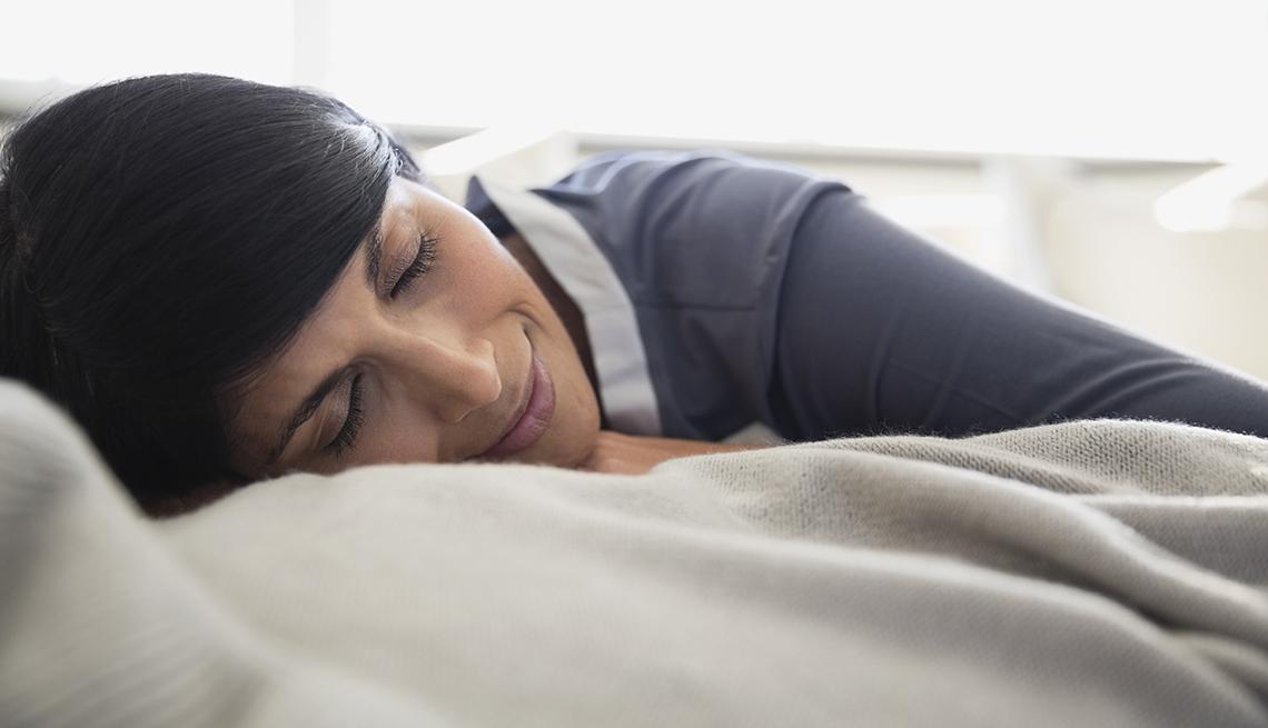 Mujer de cabello negro duerme con una sonriasa en el rostro.