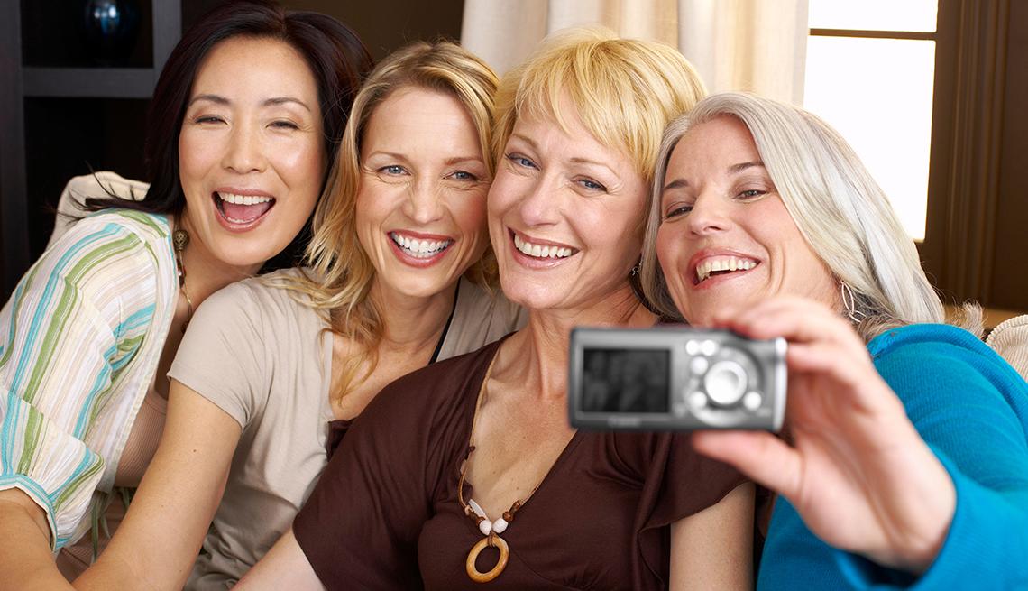 Cuatro mujeres sonríen a la cámara en un selfie.