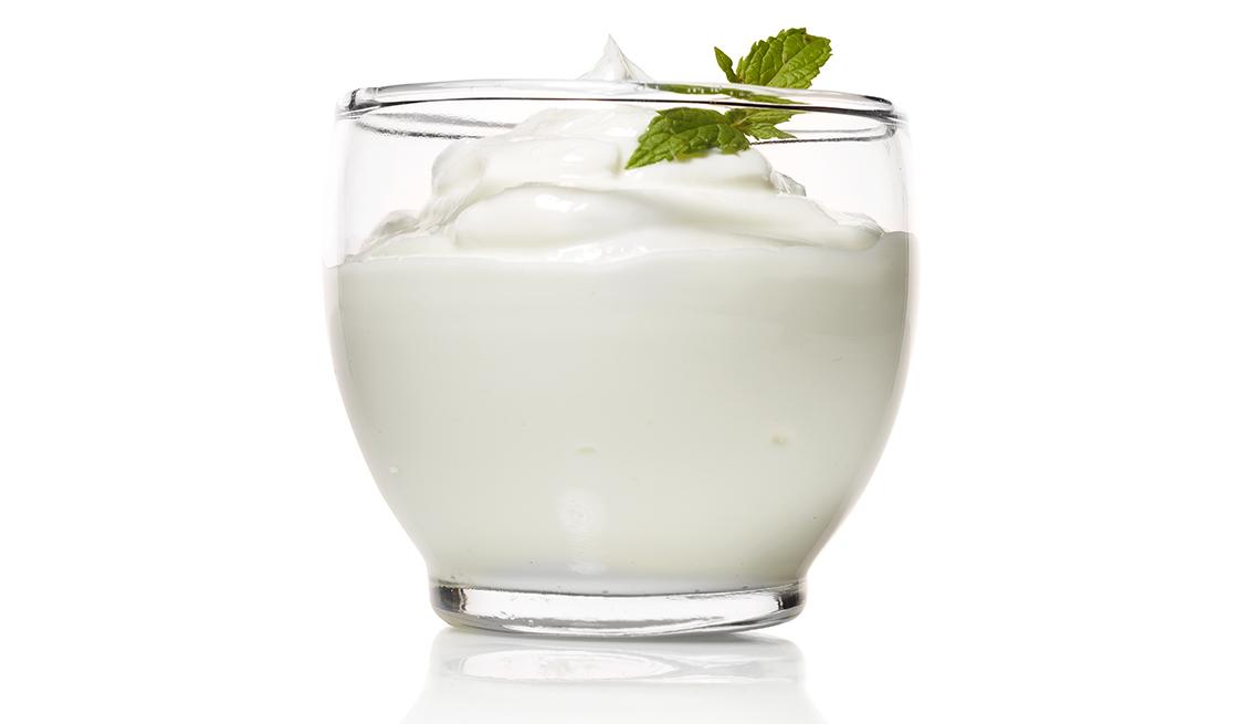Yogur en un vaso transparente con una ramita de menta.