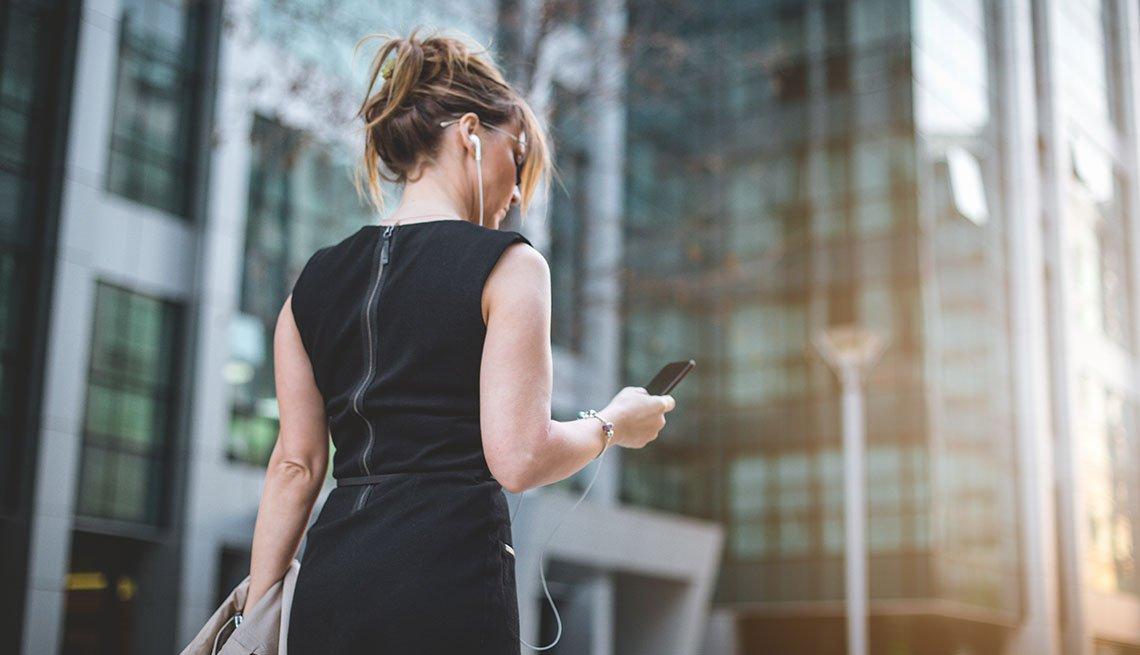Mujer caminando y mirando su celular