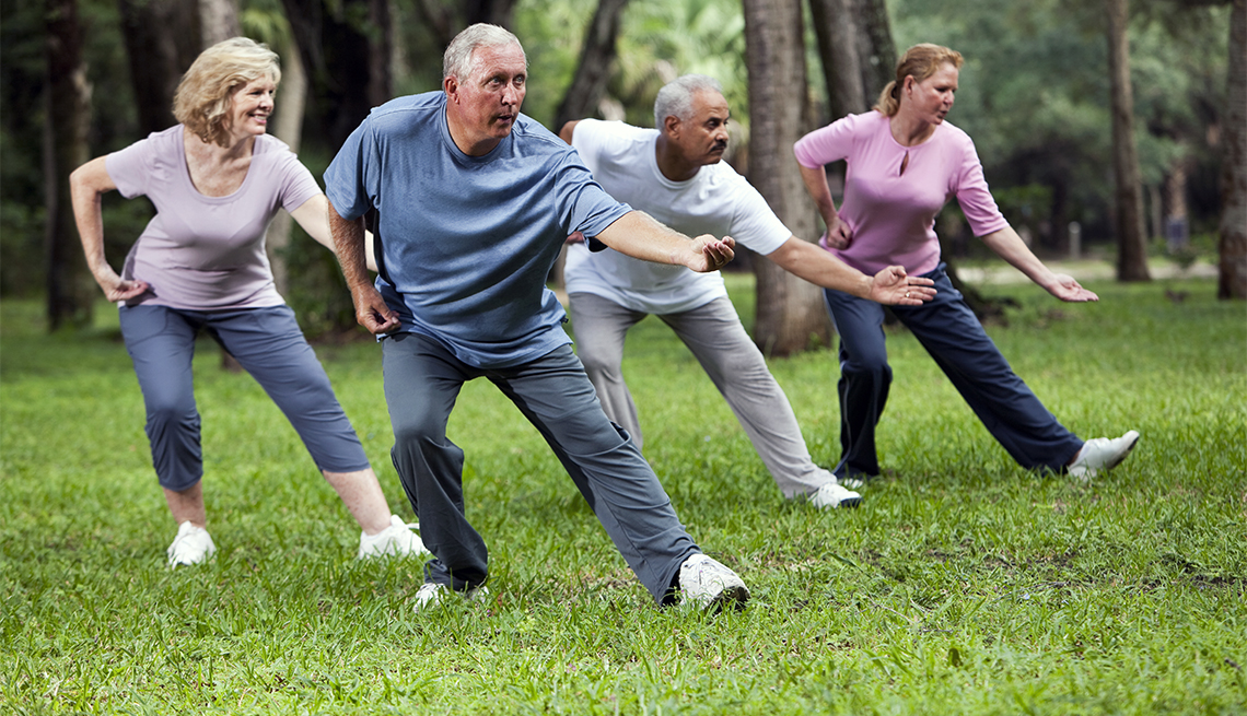 Adults practicing tai chi in park