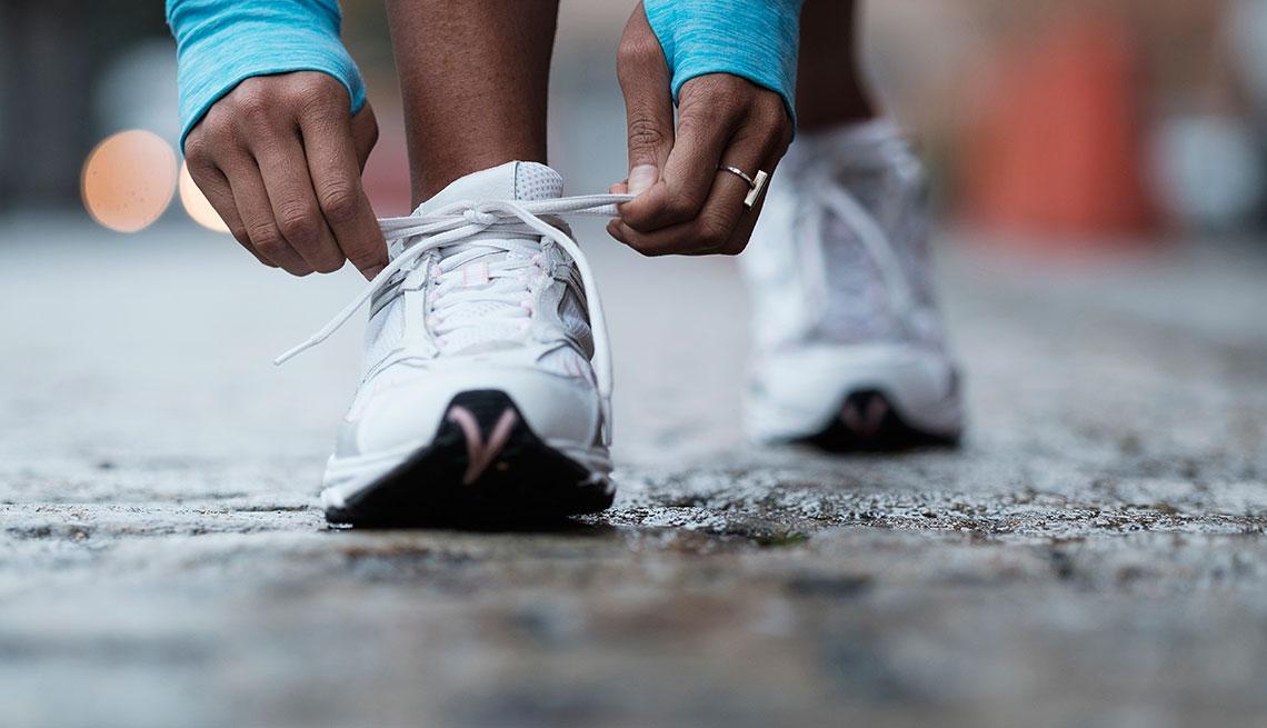 Mujer amarrando su zapatilla de correr