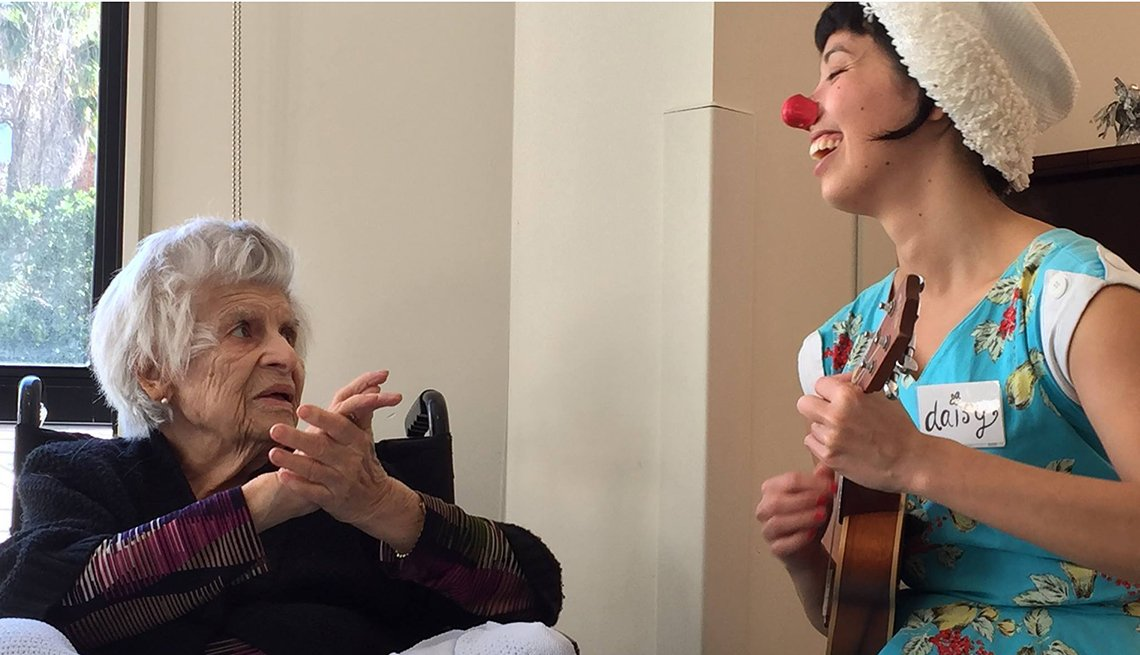 Comedian wearing clown nose and playing music entertains Alzheimer's patient