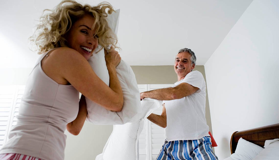 A couple having a fun pillow fight in bed