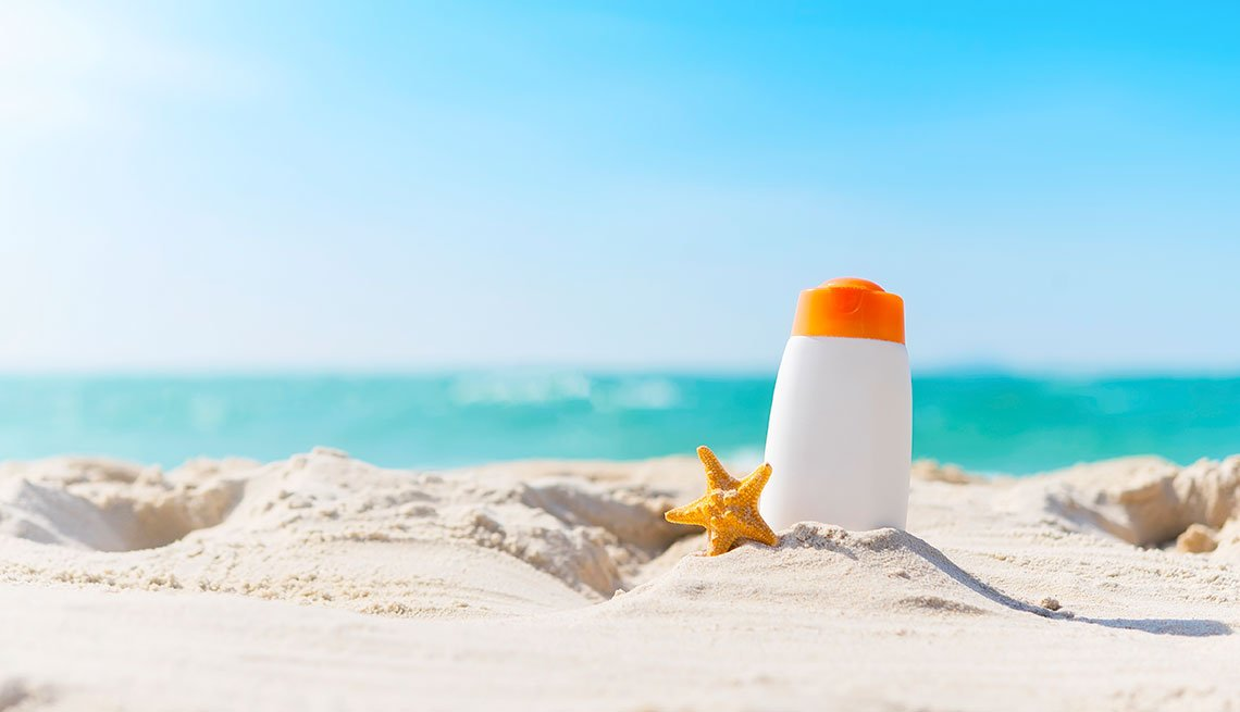 Sunblock bottle on the beach with blue sky. UV protection in summer.