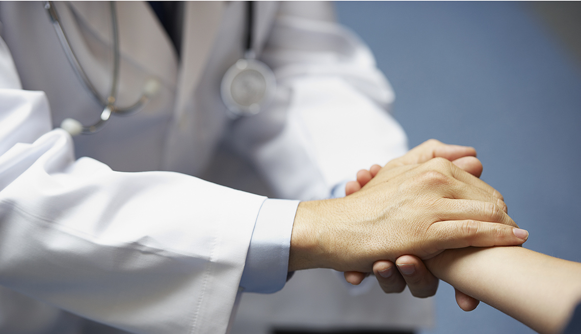 The torso of a doctor in a white lab coat with stethoscope holding a patient's hand.