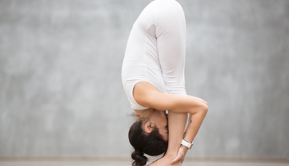 Mujer realizando el uttanasana, pose de yoga