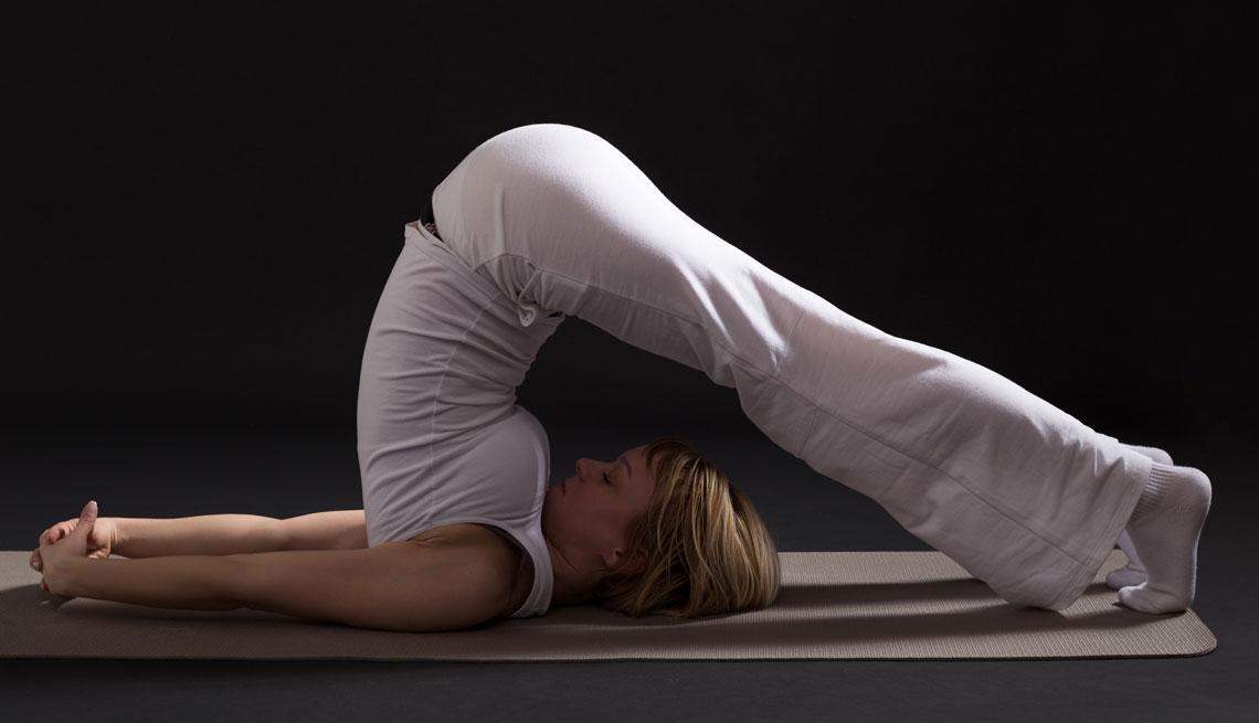 Mujer realizando el halasana, pose de yoga