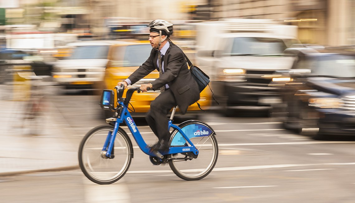 a mature man rides a bike in a city