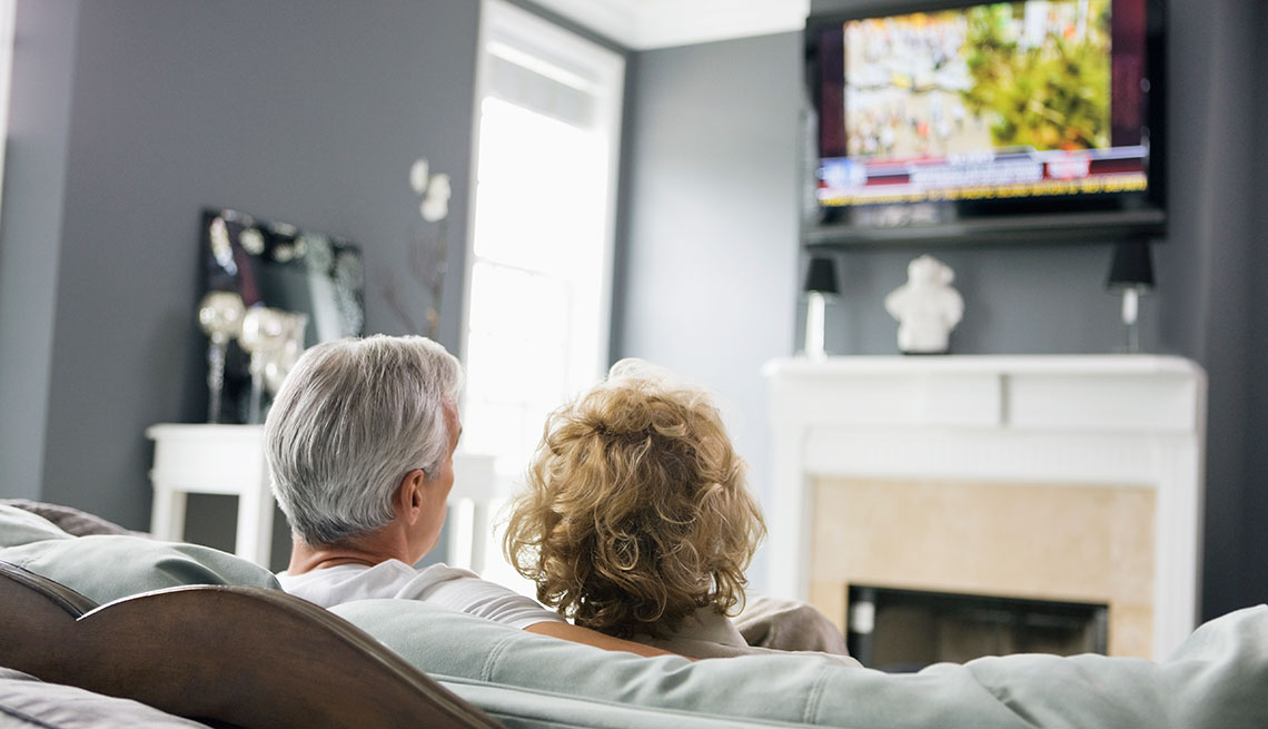 Back of heads of Man and Woman watching television in a living
