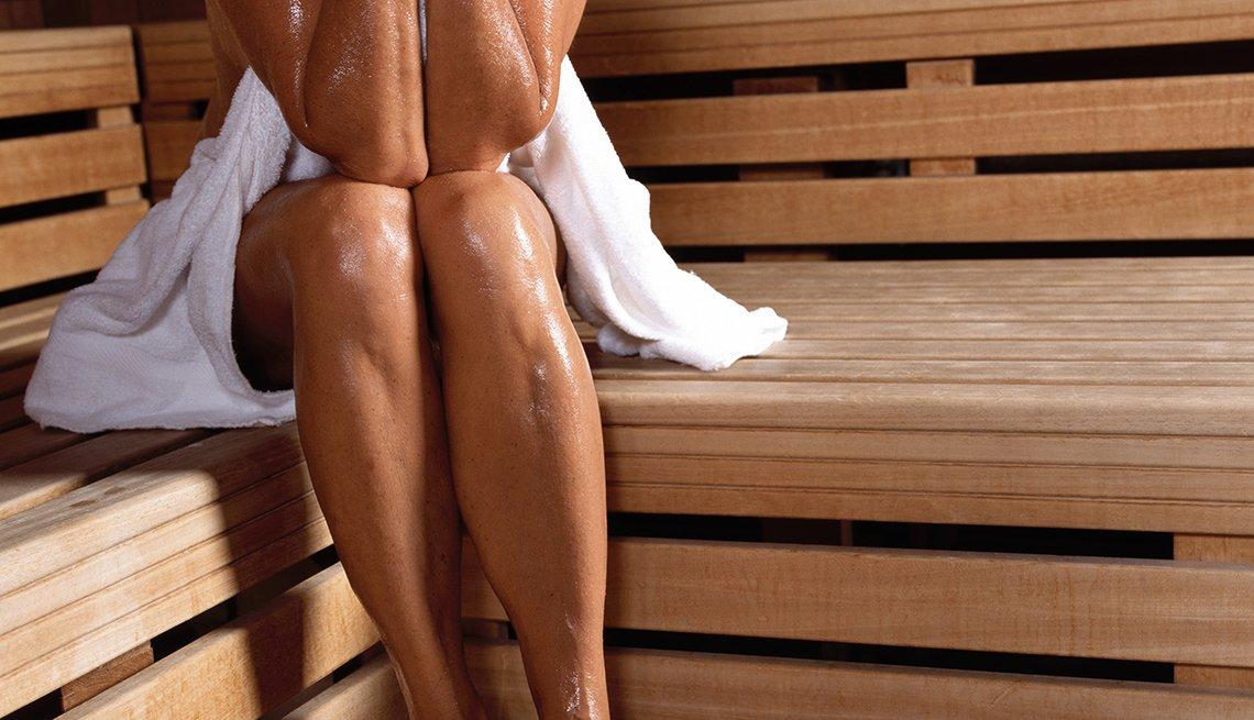 Legs of a mature woman sitting in steam sauna