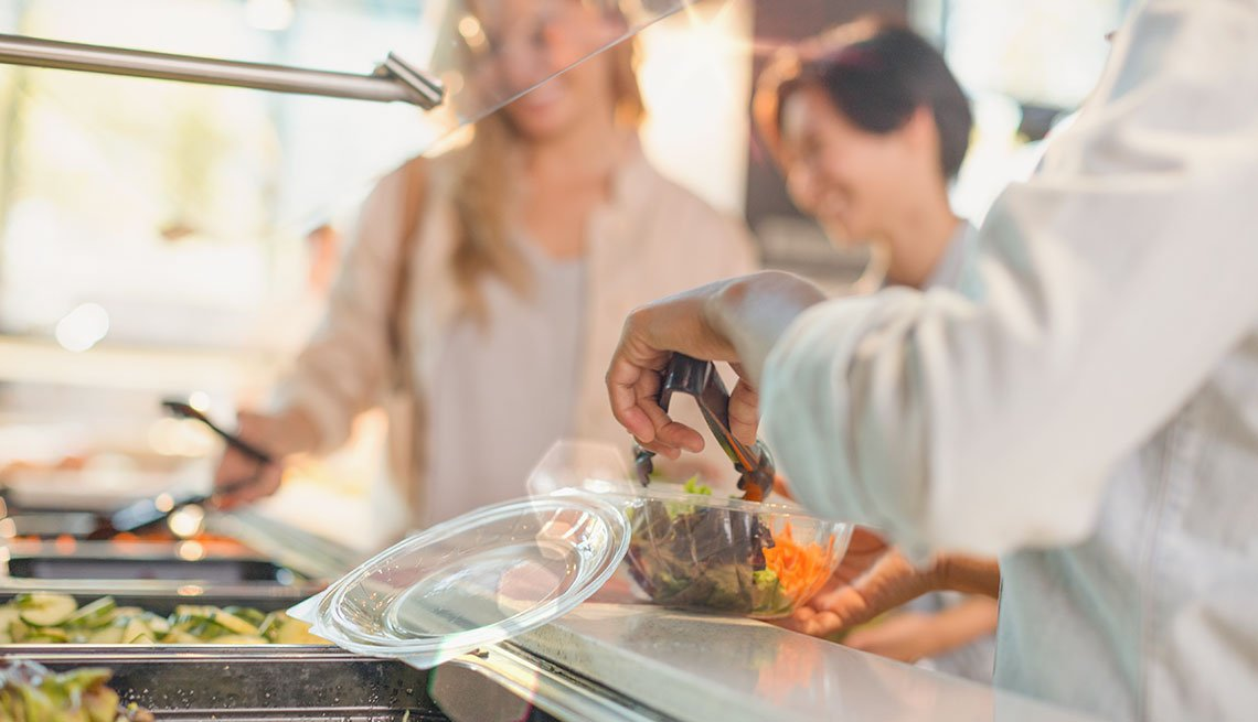 oung woman serving salad at salad bar in grocery store market