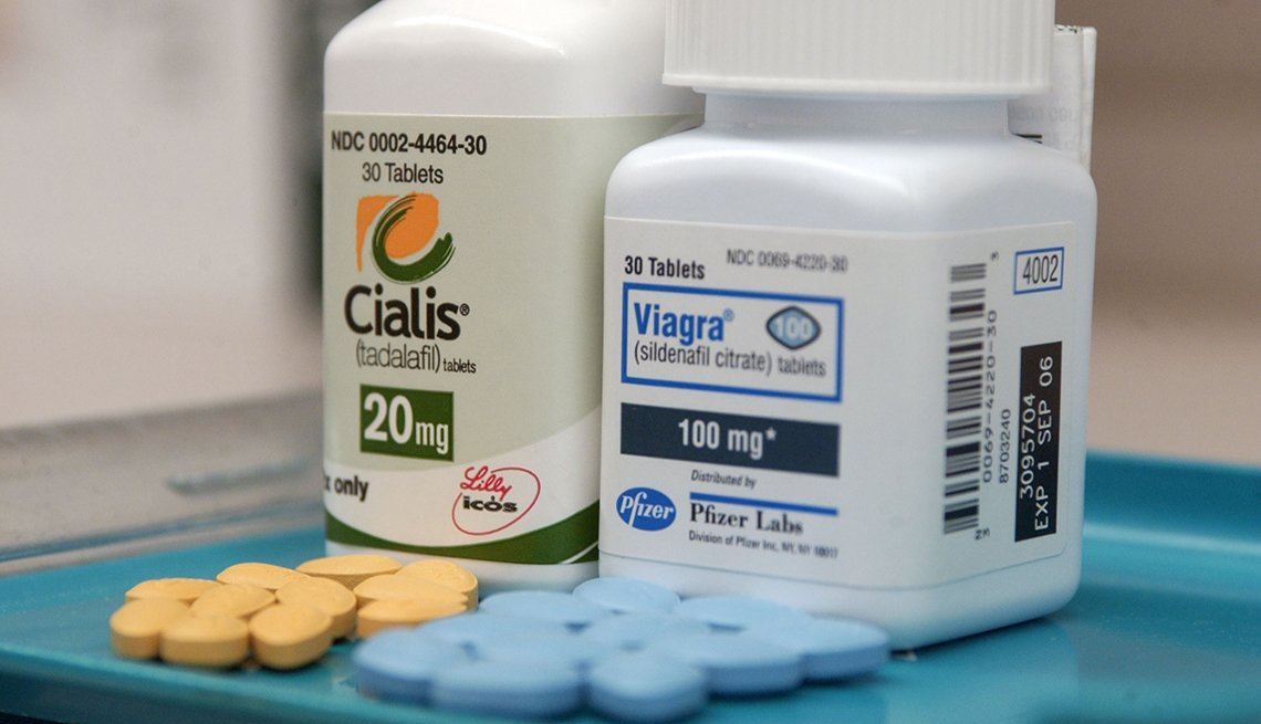 Cialis and Viagra pill bottles with pills on a tray.
