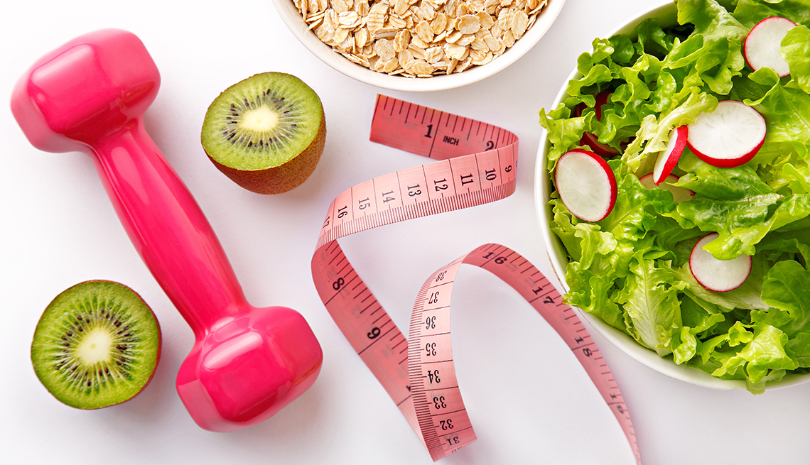 Weight loss imagery, a salad, measuring tape, avocados and a hand weight