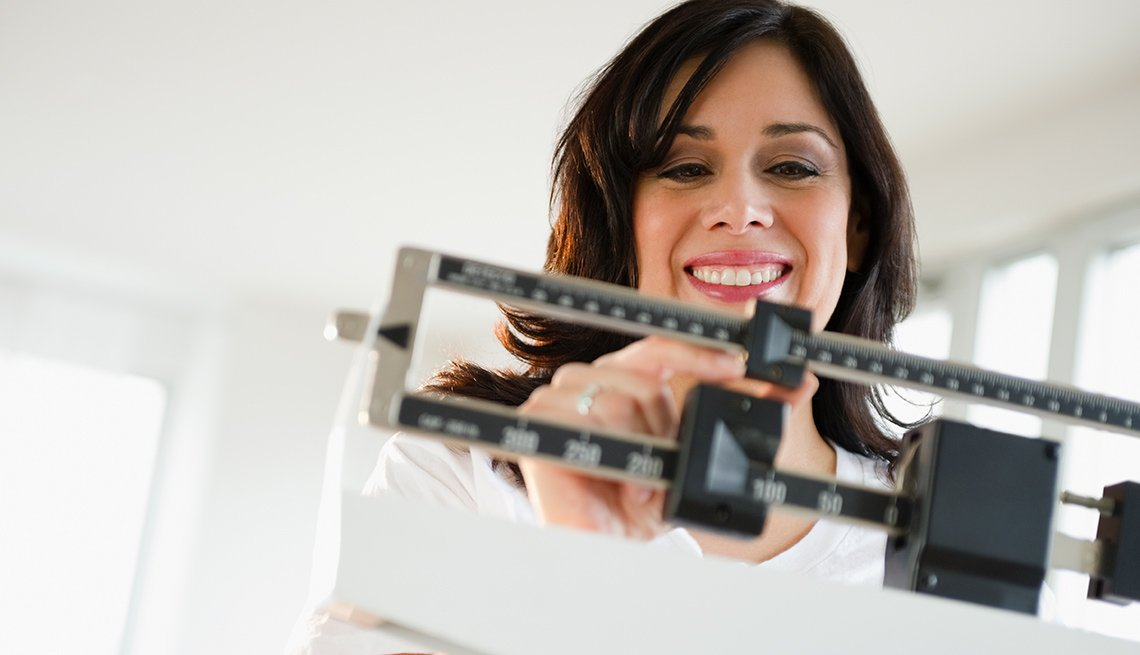 Woman adjusting weight on scale