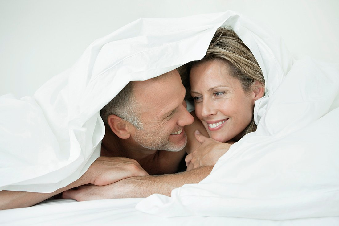A couple smiling at each other from under the covers