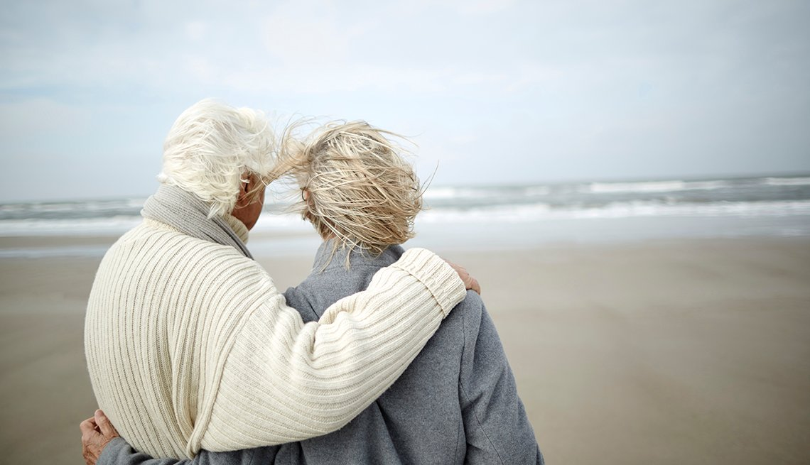 An elder couple embraces while looking at the ocean