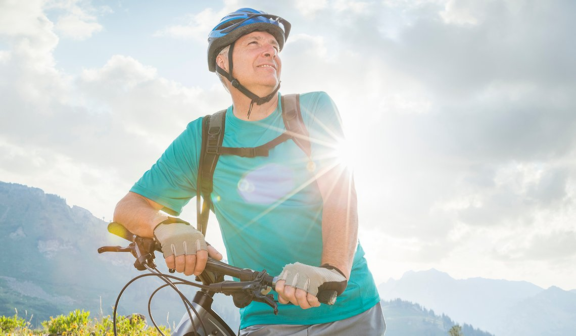 Man standing with a mountain bike in front of a mountain range.