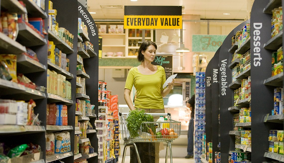 Woman standing in grocery aisle with grocery cart, looking at her shopping list.