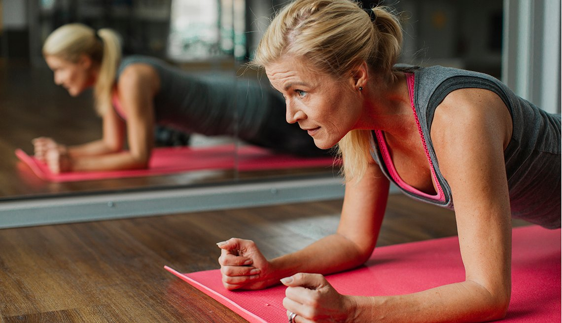 Mature woman holding a plank position on a red exercise mat.
