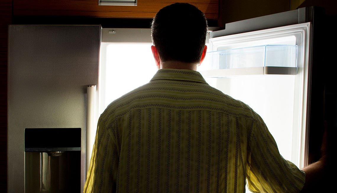 Hombre parado frente al refrigerador