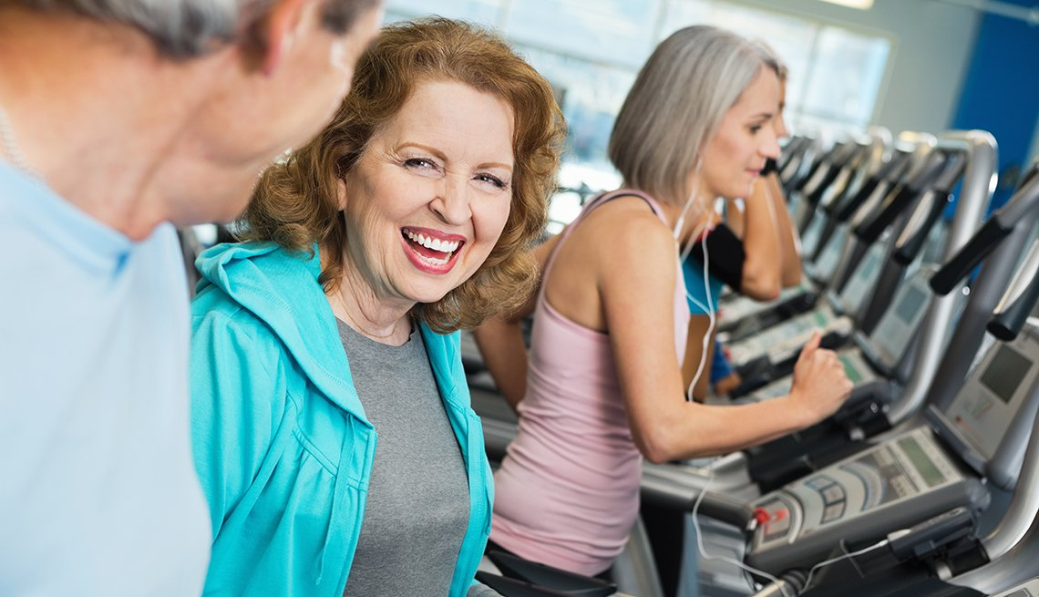 Mature woman working out in a gym, talking to a man who is also working out.  Another woman working out in the background.
