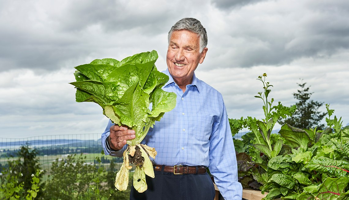 Graham Kerr, The Galloping Gourmet, standing outside on a farm, holding some greens.