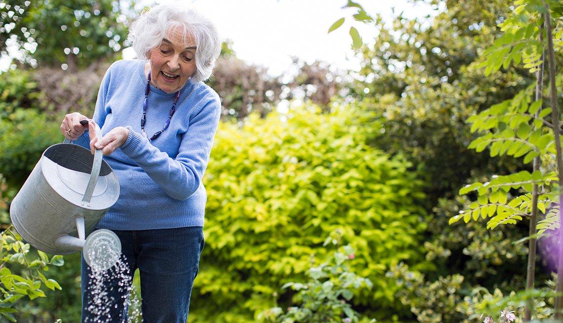 Mujer mayor regando sus plantas