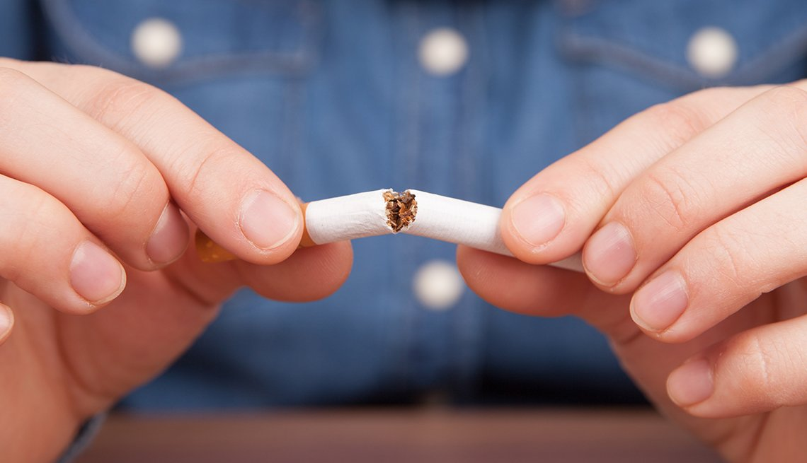 Close-up of a man's hands breaking a cigarette in half. His blue shirt in the background.