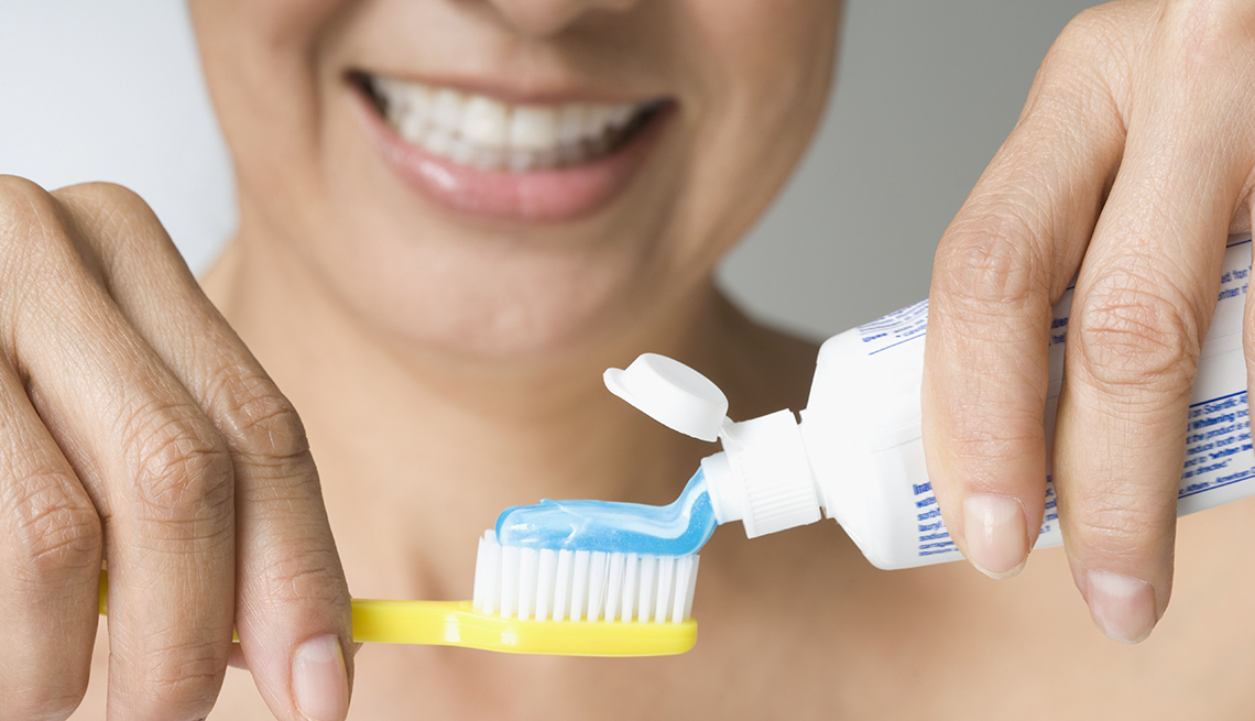 Woman holding tooth brush and toothpaste