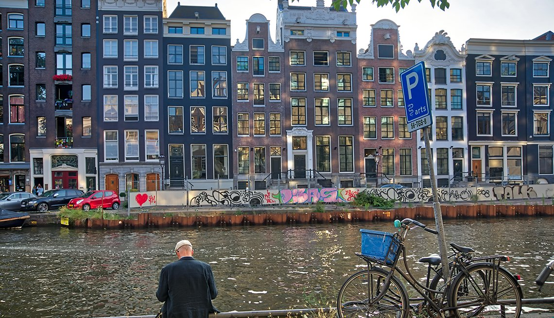 A mature man gazing down at a canal in Amsterdam, Netherland. Background view of typical dutch houses.