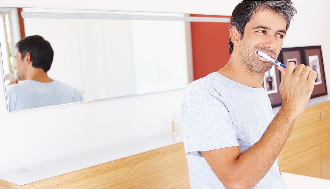Portrait of a mature man brushing his teeth in the bathroom.