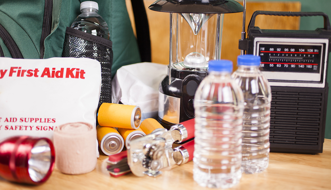 Emergency preparedness supplies, including a flashlight, backpack, batteries, water bottles, first aid kit, lantern, radio and can opener