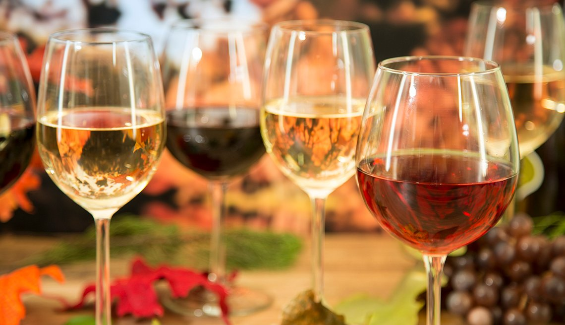 Outdoor fall setting with multiple glasses of wine sitting on a table.