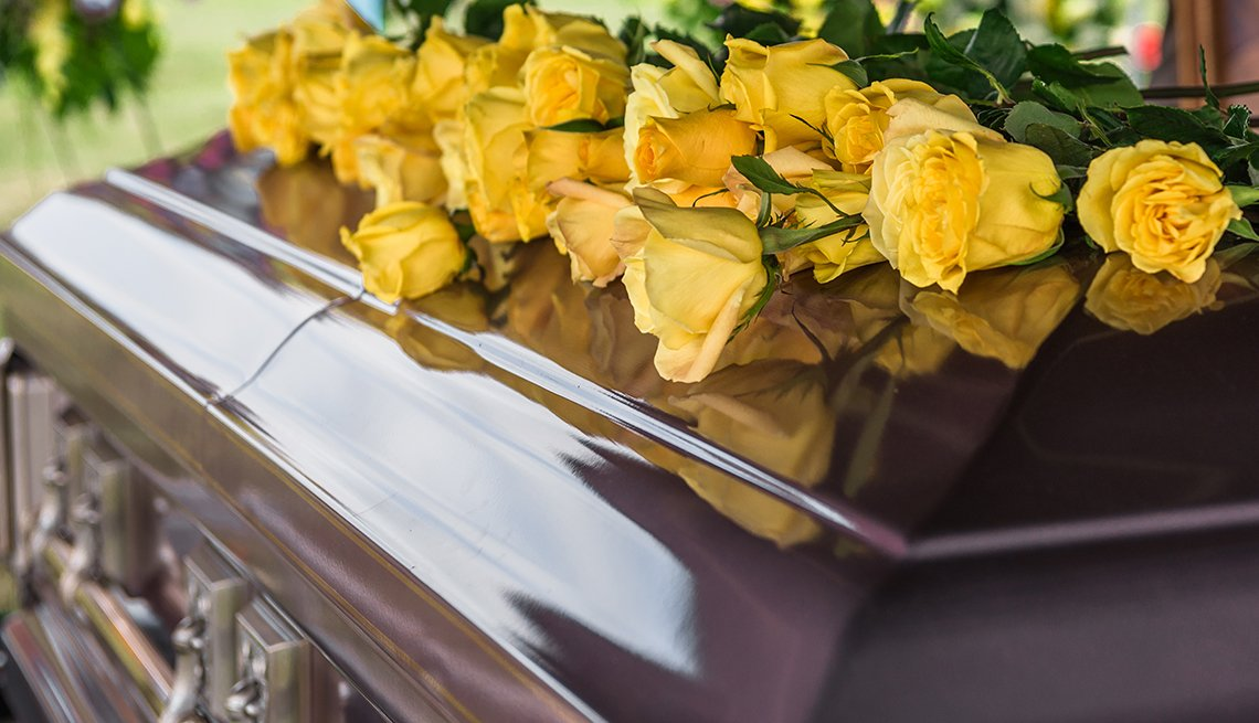 Casket in funeral service with yellow roses on top.