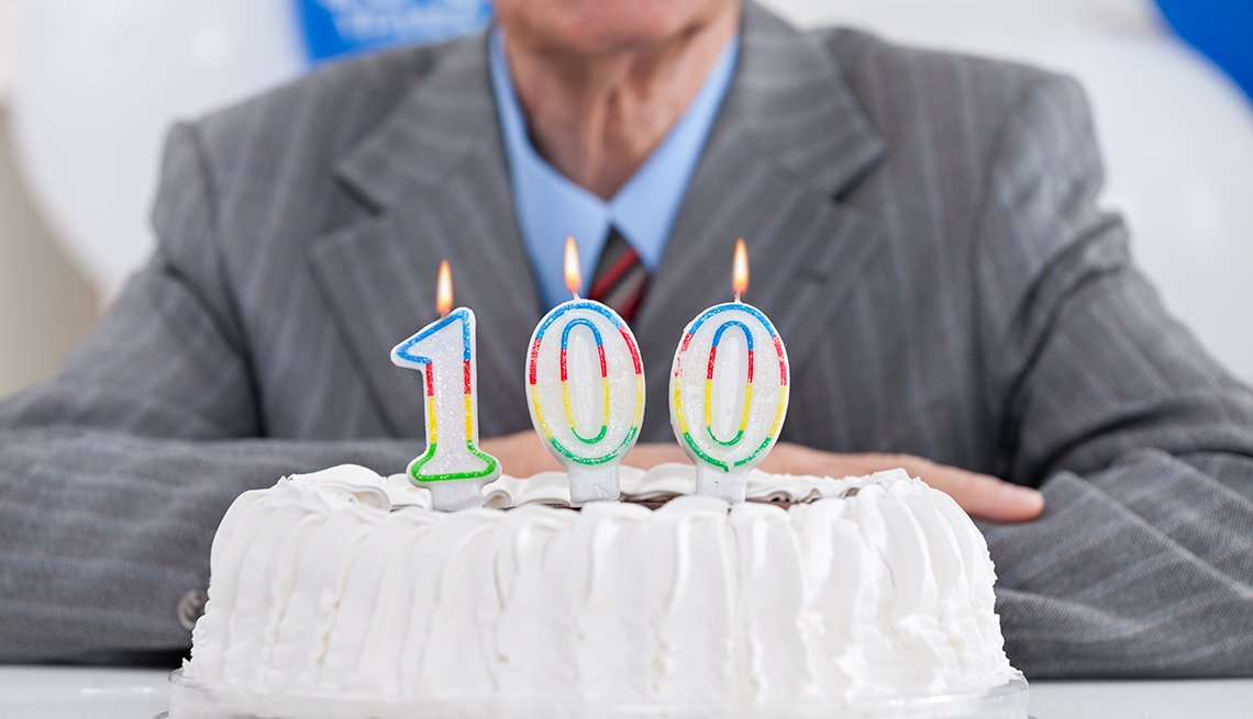 A birthday cake with lit candles for a one hundredth birthday. Older man in suit sits behind the cake.