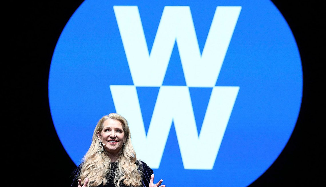 Weight Watchers CEO next to Weight Watchers new logo