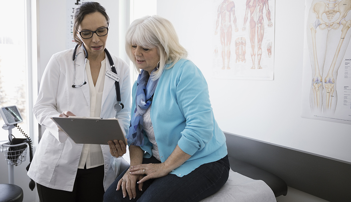 Mature woman discussing something with her doctor.
