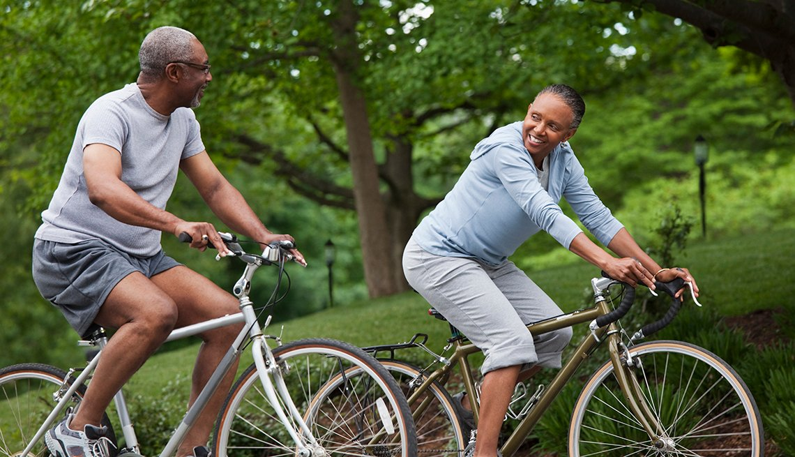 Couple riding bikes along a wooded path