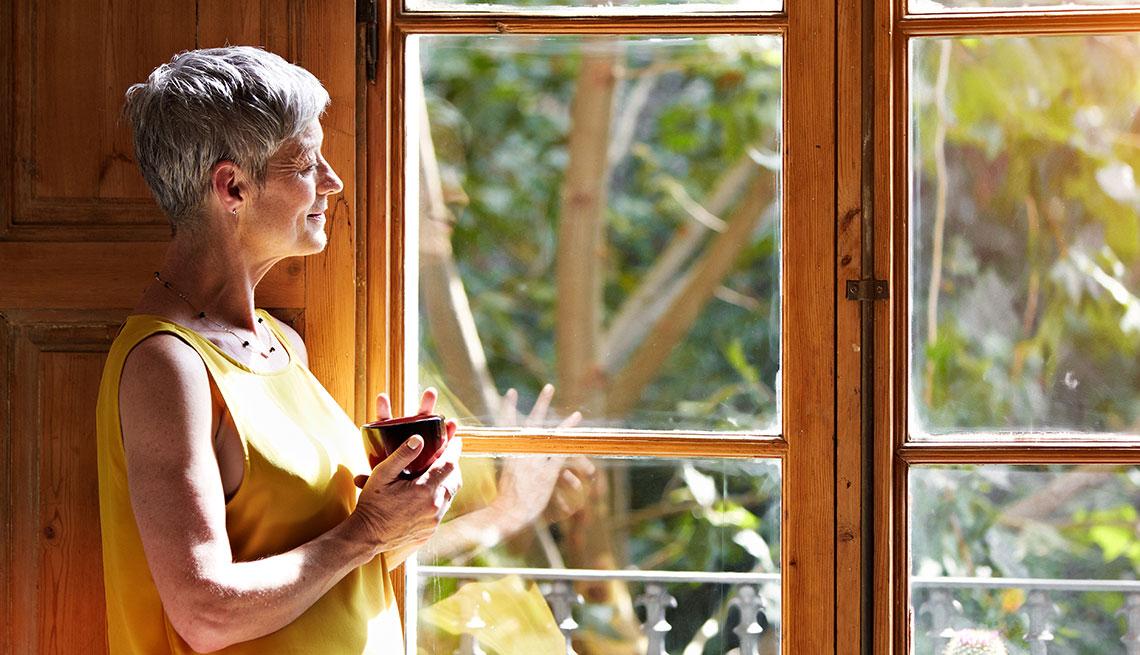 Mujer tomando café frente a una ventana