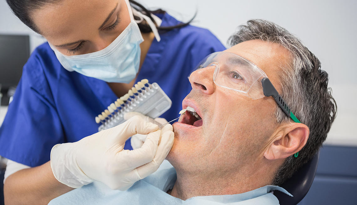 Dentist comparing tooth shade to patient's teeth