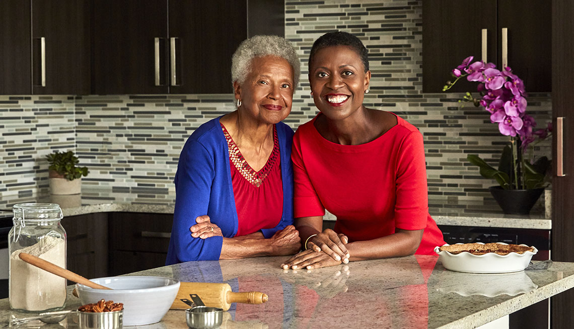 Daughter-mother cooks Tracye and Mary McQuirter leaning against a counter. A pecan pie sits next to them.