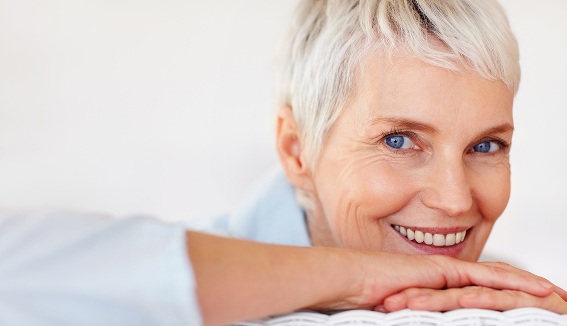 Woman smiling and resting her head on her arms