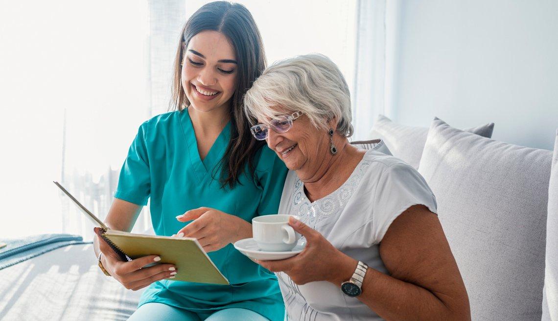 Enfermera muestra una libreta de anotaciones a una mujer mayor.