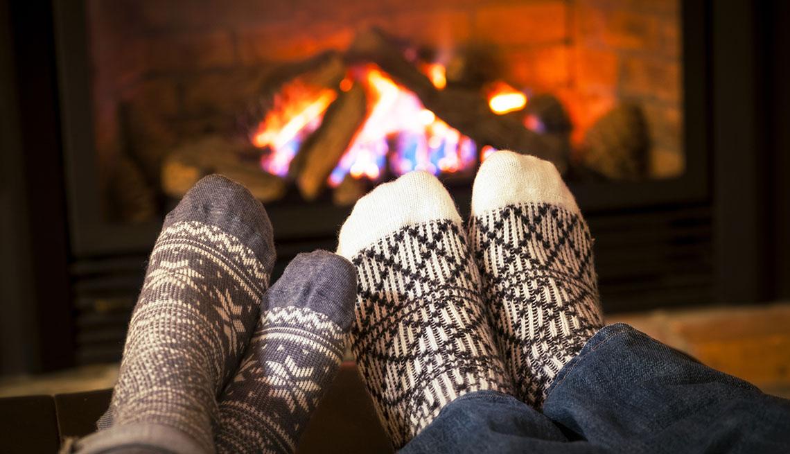 Feet in wool socks warming by cozy fireplace