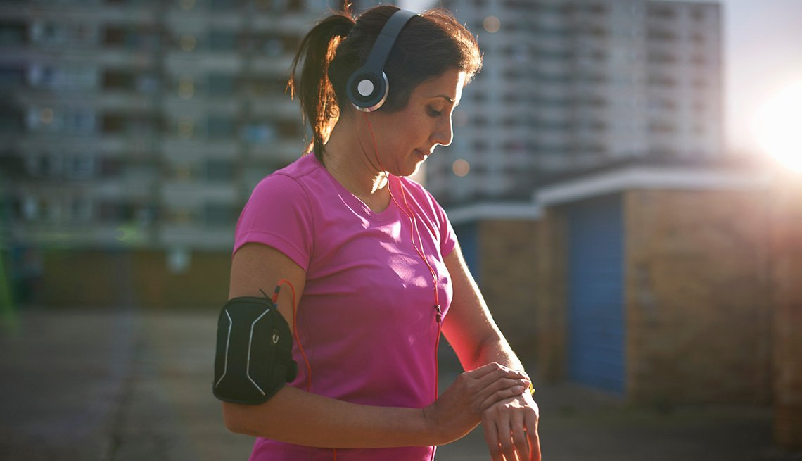 Woman outside in an urban setting, checking her watch during her workout.