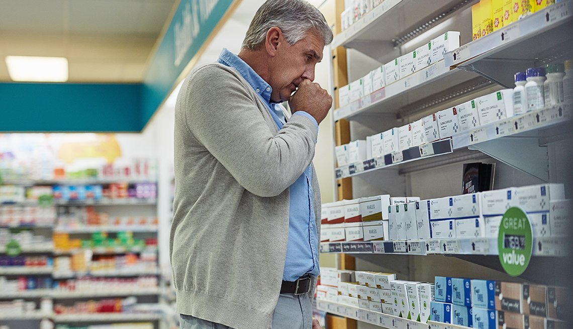 Shot of a mature man browsing the shelves of a pharmacy and coughing