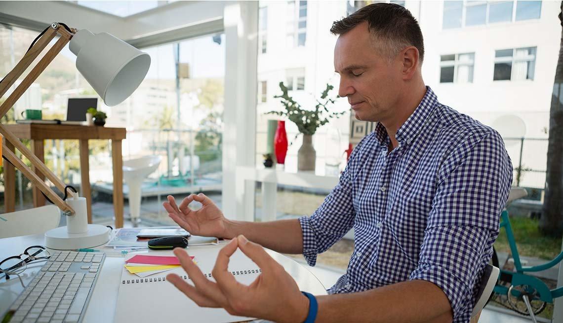 Mature man sitting at his desk at work meditating.