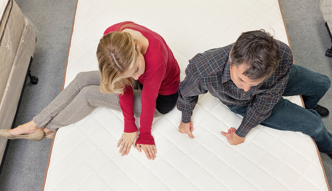 Couple testing out mattresses at a furniture store