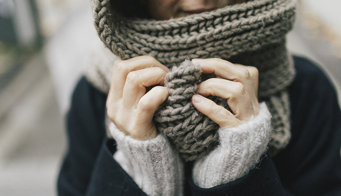 close up of Woman's hands holding knitted scarf